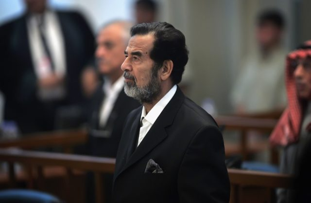 BAGHDAD, IRAQ - OCTOBER 19: Ousted Iraqi leader Saddam Hussein stands as a witness (not seen) is sworn in for testimony during his trial in the heavily fortified Green Zone October 19, 2006 in Baghdad, Iraq. Hussein and six co-defendants have been on trial since August 21, 2006 for the Anfal campaign of bombings and gas attacks against Kurdish rebels in 1987-1988. It is believed the Anfal campaign left up to 180,000 dead. (Photo by David Furst-Pool/Getty Images)