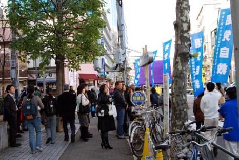 Прохожие узнают о зверствах КПК. Фото: minghui.ca