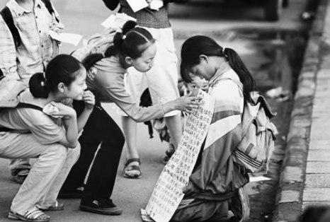 Двое девочек читают надпись на плакате девочки, просящей милостыню на улице. Фото: Великая Эпоха.