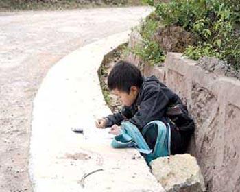 Деревенский мальчик выполняет домашнее задание – прямо на дороге. Фото с сайта secretchina.com