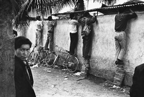 Приезжие в провинцию Хайнань из других провинций, у кого нет специальных пропусков, были схвачены, а те, кому посчастливилось убежать, заглядывают через забор и смотрят как там их родственники и друзья. Провинция Хайнань. 1992 год. Фото: Huan Yiming
