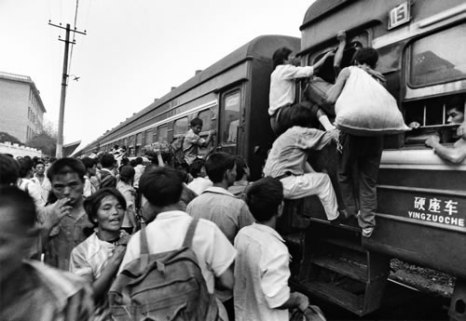 Много пассажиров, но мало поездов. Люди пытаются залазить в вагоны через окна. Город Гуанань провинции Сычуань. Август 1992 года. Фото: Zhou Guoqiang