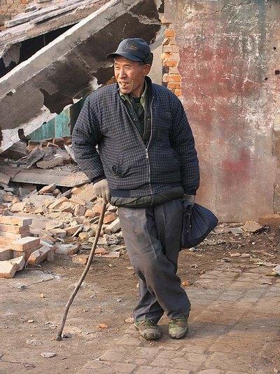 Этот мужчина стоит возле останков своего дома, который был снесён для расширения дороги. Город Биндиншань провинции Хэнань. Фото: Zhenda