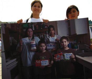 Две девочки, уроженки северной Канады, показывают картину, на которой изображена их семья. Картина в первую очередь демонстрирует высокие цены основных продуктов питания, что является распространенной проблемой для северных регионов страны. Фото: Мэтью Литтл /Великая Эпоха