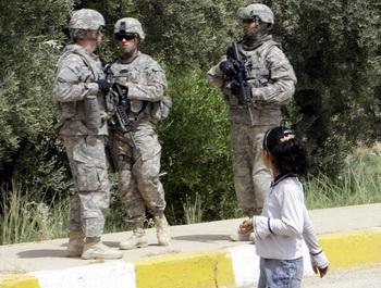 Девочка мирно прогуливается мимо солдат в Ираке. Фото: ALI AL-SAADI/AFP/Getty Images