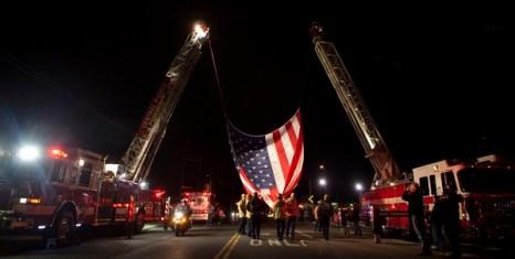 Пожарные поднимают гигантский флаг на автокране, чтобы чтить память четырех Лейквудских полицейских. Фото: Stephen Brashear/Getty Images)
