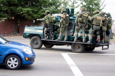 Участники команды ОМОН едут на бронированной машине, ища подозреваемого. Фото: Stephen Brashear/Getty Images