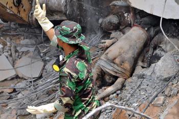 Спасатель освобождает  человека из-под развалин. Фото: ADEK BERRY/AFP/Getty Images