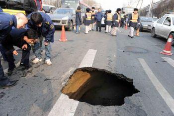 Китайские рабочие осматривают образовавшийся провал. Фото: AFP/Getty Images