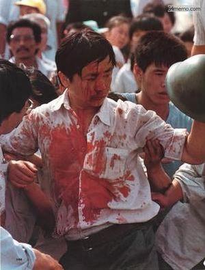 3 июня 1989 г. Напротив здания народного собрания в Пекине произошла стычка горожан с солдатами. Избитый солдатами рабочий весь в крови держит каску, которую ему удалось сорвать с кого-то из солдат во время потасовки. Фото с 64memo.com