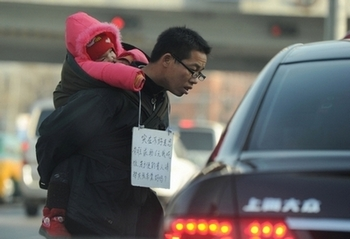 На улице Пекина мужчина с ребёнком просит милостыню. Фото: PETER PARKS/AFP/Getty Images