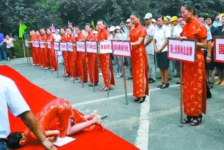 Во время церемонии открытия спартакиады девушки с табличками падают в обморок из-за жары. Фото с kanzhongguo.com