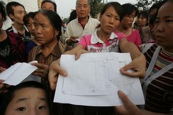 Люди показывают медицинские заключения, в которых указана степень отравления свинцом. Фото с epochtimes.com