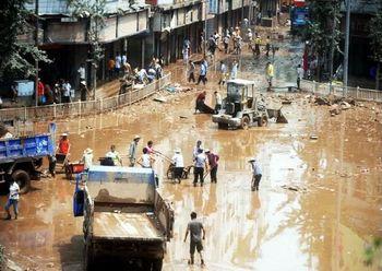 Жители посёлка Гуанан провинции Сычуань очищают улицы от грязи после наводнения. Фото с epochtimes.com
