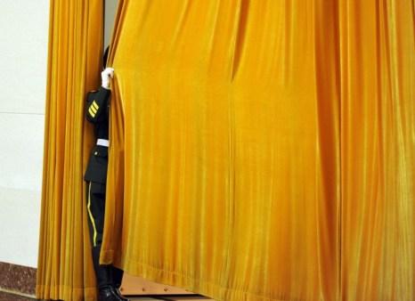 Китайские охранник задёргивает занавес перед церемонией в Большом Народном Зале, Пекин, 9 апреля 2012 года. Фото: Liu Jin/AFP/Getty Images