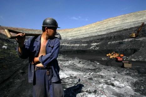 Шахтёр на фоне угольного карьера, 19 августа 2006 года, Внутренняя Монголия, Китай. Фото: China Photos/Getty Images