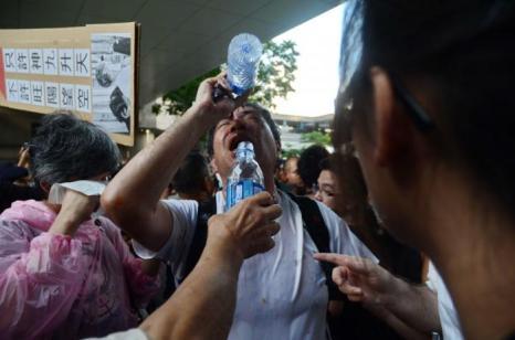 Участники акции протеста ополаскивают глаза, поражённые перцовым аэрозолем, водой. Фото: Liang Lusi/The Epoch Times
