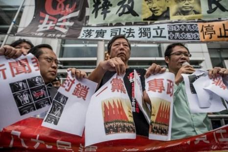 Продемократический законодатель Ли Чок-ян (посередине) разрывает фото, на котором изображены китайские лидеры на съезде, в знак протеста против политики центрального правительства КНР, Гонконг, 8 ноября 2012 года. Фото: Phillipe Lopez/AFP/Getty Image