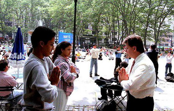 Денис Боди, последователь Фалуньгун, учит упражнениям прохожих, которые проявили интерес к занятиям, 13 мая 2000 года. Фото с сайта minghui.org