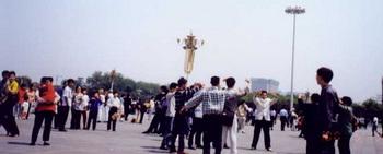 Офицер в штатском спешит арестовать последователей Фалуньгун, которые в первый День Фалунь Дафа, 13 мая 2000 года, выполняют упражнения на площади Тяньаньмэнь,  Пекин, Китай. Фото с сайта minghui.org