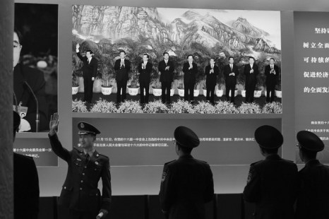 Полицейский позирует на фоне фото Ху Цзиньтао, посещающего выставку в Пекине. По сообщениям, количество членов Политбюро, самого влиятельного органа власти в Китае, может сократиться с 25 человек до 22, а число членов Постоянного комитета Политбюро уменьшилось с 9 до 7 человек. Фото: Feng Li/Getty Images