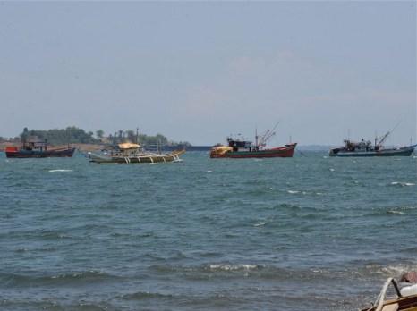 Рыбацкие лодки, прозванные местными жителями «материнскими», которые используются для перевозки рыбы, пойманной на мелководье Скарборо, к северу от Манилы, выходят в  Южно-Китайское море 10 мая 2012. В течение многих лет филиппинские и китайские рыбаки мирно делили здесь богатый улов, но сегодня угрозы, преследования и страх заменили морскую дружбу. Фото: Ted Aljibe/AFP/Getty Images