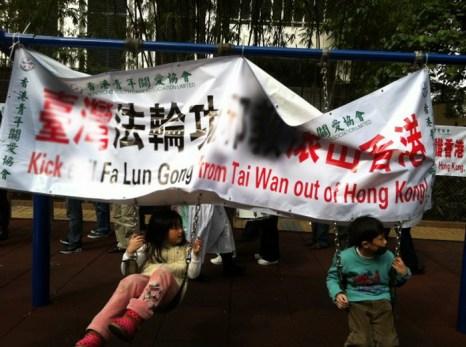 Дети катаются на качелях, к которым Ассоциация содействия молодёжи Гонконга прицепила свой баннер, содержащий нападки на Фалуньгун. На заднем плане — другой их баннер. Фото: The Epoch Times