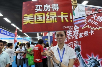 """Реклама в Пекине: «Купи квартиру, получи """"зелёную карту"""" США». Фото: AFP/AFP/Getty Images"""