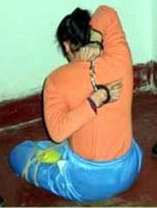 Инсценировка пытки «нести меч на спине». Фото: minghui.org
