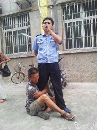 Уличный торговец держит за ногу городского контролёра, который его избил. Провинция Шэньси. Июль 2012 год. Фото: weibo.com