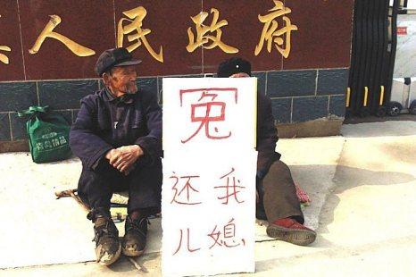 Пожилые супруги сидят возле здания правительства, требуя освободить их невестку. На их плакате написано: «Несправедливо обиженный. Верните мою невестку». А за их спиной на стене символически красуется надпись «народное правительство». Фото с minghui.org