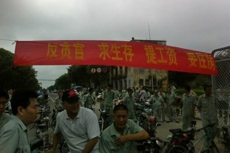 Надпись на плакате: «Против коррупции, хотим условий для жизни, повышения зарплаты, жильё». Забастовка рабочих. Провинция Гуандун. Май 2013 года. Фото с epochtimes.com