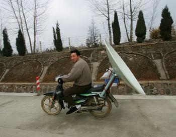 Китаец везёт спутниковую телевизионную антенну.   2005 год, провинция Аньхой (Китай). Фото: Канкан Чу / Getty Images