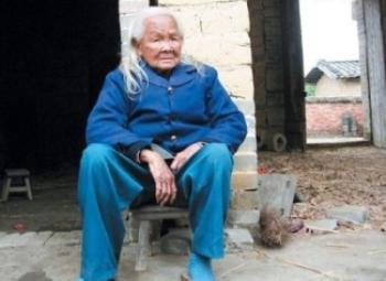«Ожившая» Ли Сюфэнь сидит возле дверей своего дома. Фото с epochtimes.com