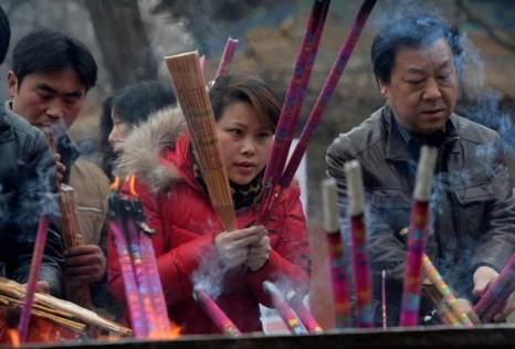 Китайцы возжигают благовония в храмах на Новый год. Январь 2014 года. Фото: MARK RALSTON/AFP/Getty Images