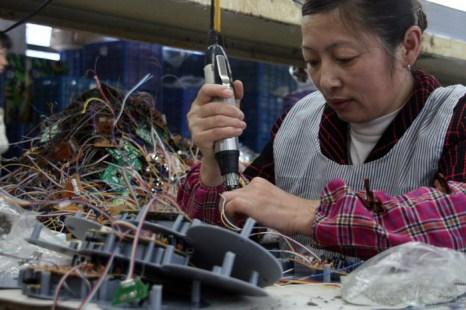 Женщина трудится на фабрике в юго-восточной китайской провинции Фуцзянь, 2 апреля 2011 года. Даже самые простые электронные приборы, сделанные в Китае, могут быть с сюрпризом  шпионским устройством. Фото: STR/AFP/Getty Images