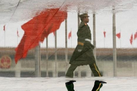 Это перевернутое изображение в луже отражает полицейского, патрулирующего на площади Тяньаньмэнь во время встречи провинциальных депутатов в Большом зале народных собраний в Пекине 08 марта 2006 года. Фото: MARK RALSTON/AFP/Getty Images