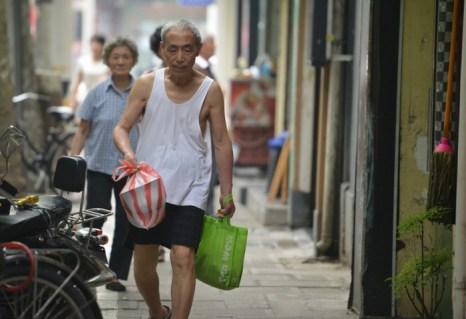 Пожилой мужчина с покупками на улице в Шанхае, 1 июля 2013 года. Внутреннее потребление пока не способно заменить увядающий экспорт в самой населённой стране мира. Фото: Peter Parks /AFP/Getty Images