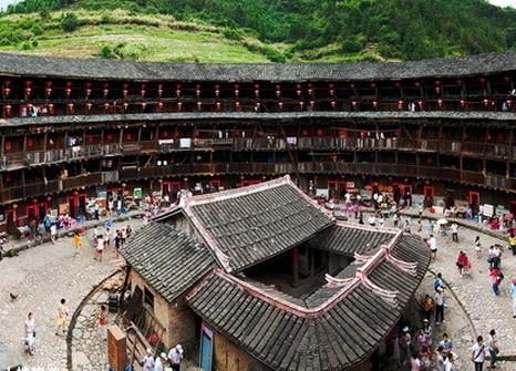 Глиняные жилища — самые красивые и уникальные образцы архитектуры ханьцев. Жёлтый цвет их глиняных стен гармонирует с зелёными плантациями риса, растущими вдали. Фото: Xiao Yue