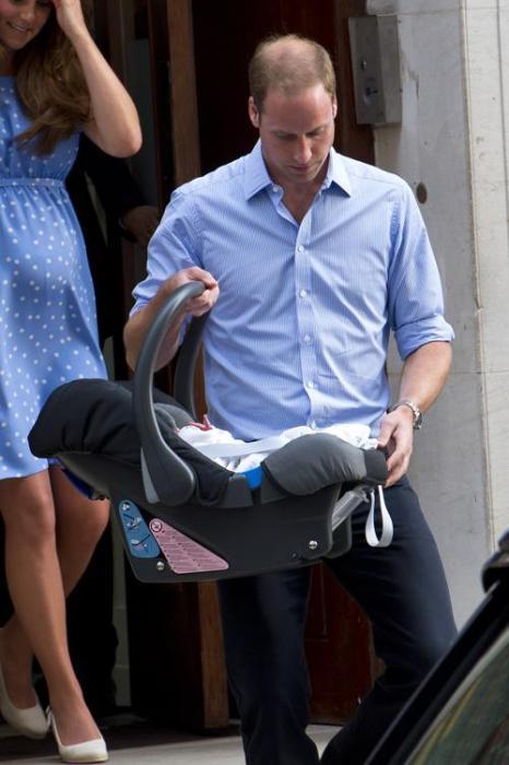 Герцог Кембриджский принц Уильям и его супруга герцогиня Кэтрин показали новорождённого принца Великобритании, после того как мама с ребёнком выписались из госпиталя 23 июля 2013 года. Фото: Oli Scarff/Getty Images