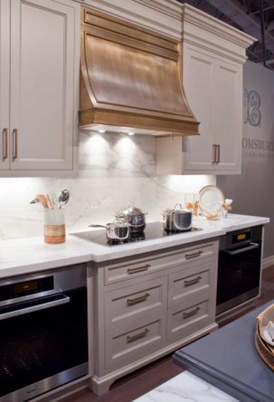 Эта кухня представляет сочетание мягких золотых акцентов с элементами из серебра и нержавеющей стали, два оттенка мягкого серого цвета, дерево и белый мрамор. Фото: Bloomsbury Fine Cabinetry