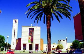 Начните отсюда: Сабаудия расположена в центре Латины, что очень удобно для желающих исследовать эту область. На снимке показана приходская церковь на фоне пальм. Город также славится своими пляжами. Фото: Fototeca Enit/Vito Arcomano