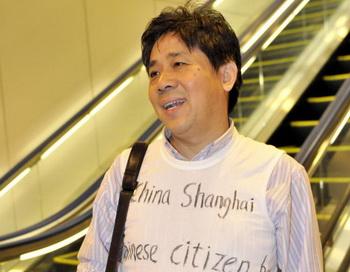 Китайский правозащитник Фэн Женху в футболке, на которой написана его апелляция, разговаривает с корреспондентом AFP в международном аэропорту Нарита в  Японии. 12 ноября. Фото: Yoshikazu Tsuno / AFP / Getty Images
