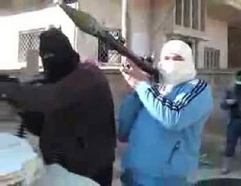 На видео, выложенном в YouTube 29 января, вооруженные люди, якобы солдаты Свободной Сирийской Армии (FSA), стоят на страже в центре сирийского города Растан, провинция Хомс. Фото: AFP/Getty Images