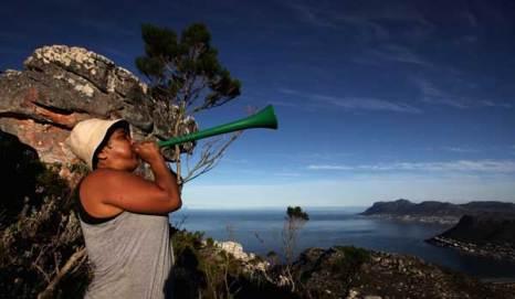 Женщина трубит в рожок «Вувузела» (шумовой символ футбола в Южной Африке) с горы «Столовая гора» в Национальном парке Кейптауна. Фото: John Moore/Getty Images