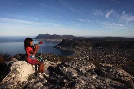 Девочка трубит в рожок «Вувузела» (шумовой символ футбола в Южной Африке) с горы «Столовая гора» в Национальном парке Кейптауна. Фото: John Moore/Getty Images