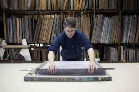 Шон Столл вручную наносит краску на обои, используя шёлковый сетчатый трафарет. Фото: Samira Bouaou/Epoch Times