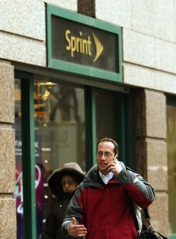 Прохожий разговаривающий по сотовому телефону в Нью-Йорке, проходит мимо магазина Sprint на 42-й улице. 15 января 2008. Фото: Don Emmert/AFP/Getty Images