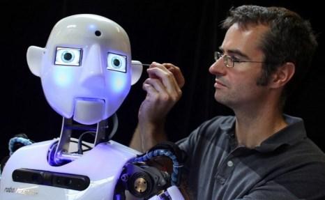 Дизайнер и инженер компании Engineered Arts Маркус Холд (на фото не виден) работает над уже почти собранными роботами RoboThespian 30 июля 2013 года в Пенрине, Великобритания. Фото: Matt Cardy/Getty Images