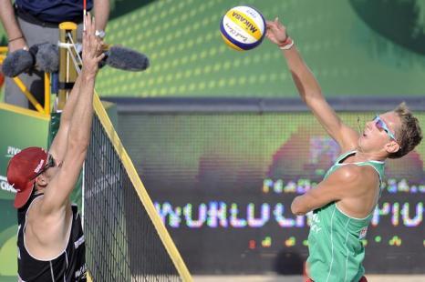 Константин Семёнов (п) и американец Джейкоб Гибб (л) на третьей встрече группового этапа чемпионата мира по пляжному волейболу в Польше 4 июля 2013 года. Фото: Adam Nurkiewicz/Getty Images